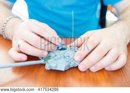 A Man Assembles A Plastic Tank Model Toy, Assembles A Tank Turret