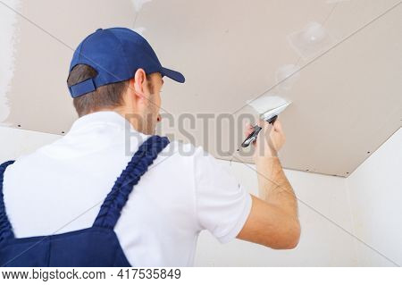 A Uniformed Worker Puts Putty On The Caps Of The Screws On The Ceiling Made Of Drywall Sheets.