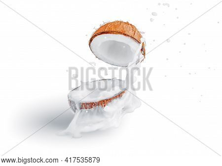Two Halves Of Coconut With The Pulp Fly Apart With A Splash Of Coconut Milk On A White Isolated Back