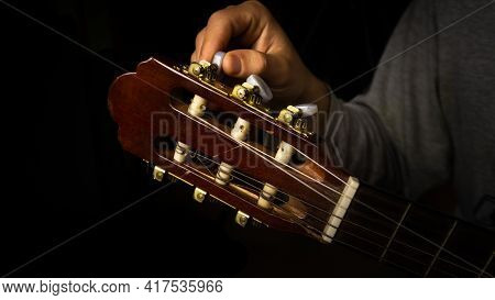 Man Tuning The Guitar In A Room With Blackbackground