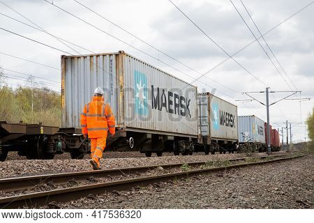 Doncaster, Uk - April, 4, 2021.  A Railway Worker Inspecting A Maersk Shipping Container Freight Tra