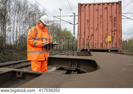A Railway Worker Examining And Maintaining A Freight Train With Shipping Containers And Copy Space