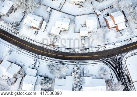 street in a residential area of Fort Collins in northern Colorado after springtime snowstorm, aerial view