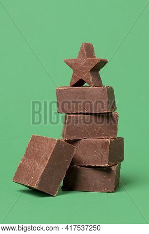 Pieces Of Chocolate Fudge Stacked On A Green Table. Slices Of Homemade Fudge In A Stack Isolated On