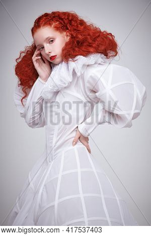 Portrait of a refined female model with lush red curly hair posing in a long white art dress on light gray background. Art fashion.