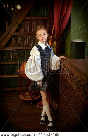 Full length portrait of a girl child in elegant classic school uniform standing in a luxurious vintage library interior. Kid's school fashion.