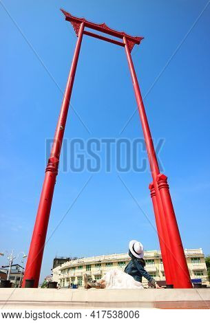 Woman In Hat Looking Up To The Giant Swing Called Sao Ching Cha, Old Teak Wood Swing Used In Religio