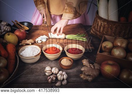 Korean Woman Is Wearing A Traditional Hanbok, She Making Kimchi Which Is A Fermented Food Preservati