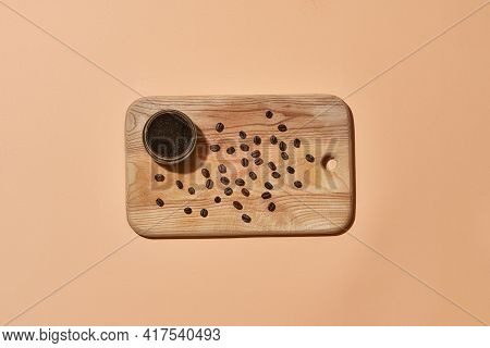 Coffee Beans Lying Beside Natural Exfoliating Scrub In Can On Wooden Board On Light Orange Backgroun