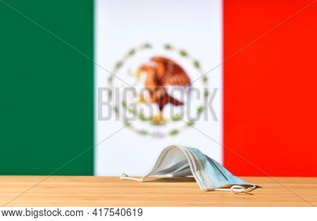 A Medical Mask Lies On The Table Against The Background Of The Flag Of Mexico. The Concept Of A Mand