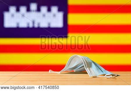 A Medical Mask Lies On The Table Against The Background Of The Flag Of Balearic Islands. The Concept