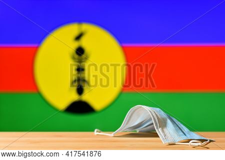 A Medical Mask Lies On The Table Against The Background Of The Flag Of New Caledonia. The Concept Of