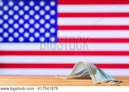 A Medical Mask Lies On The Table Against The Background Of The Flag Of Usa. The Concept Of A Mandato