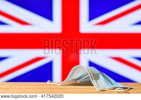 A Medical Mask Lies On The Table Against The Background Of The Flag Of Great Britain. The Concept Of