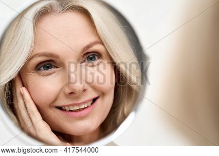 Happy Middle 50 Years Aged Woman With Blond Hair Looking At Mirror Reflection Examining And Enjoying