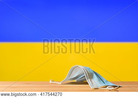 A Medical Mask Lies On The Table Against The Background Of The Flag Of Ukraine. The Concept Of A Man