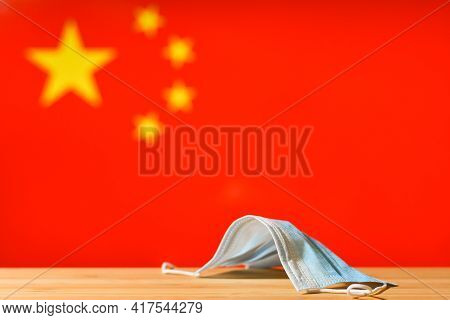 A Medical Mask Lies On The Table Against The Background Of The Flag Of China. The Concept Of A Manda
