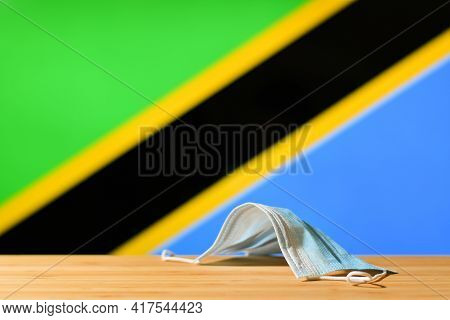 A Medical Mask Lies On The Table Against The Background Of The Flag Of Tanzania. The Concept Of A Ma