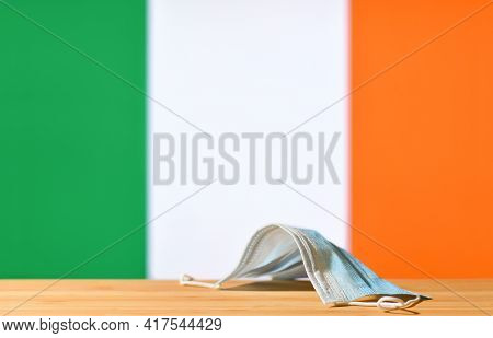 A Medical Mask Lies On The Table Against The Background Of The Flag Of Ireland. The Concept Of A Man