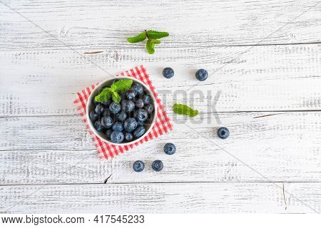 Bowl Of Fresh Blueberries On White Wooden Table. Organic Food Blueberries And Mint Leaf For Healthy