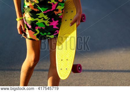 Defocus Girl Holding Yellow Penny Board. Front View. Youth Hipster Culture. Child Hands Holding Shor