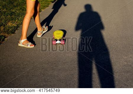 Defocus Little Child With Penny Skateboard On Path In Park. Boy And Girl Rides A Penny Board In Suns