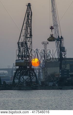 Sunset With Industrial Shipyard Cranes In Dusk