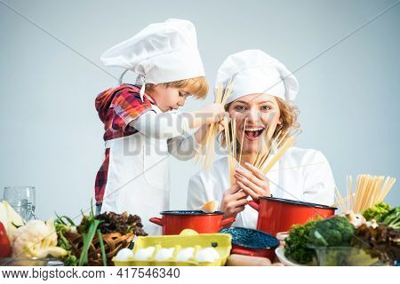 Mom And Kid With Smiling Face Cooking Spaghetti Together. Mother Teaches Son To Cook.