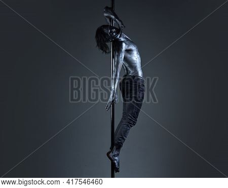 Art Sexy Man Body. Performance Concept. Man With Nude Torso Covered With Silver Paint. Guy Hanging O