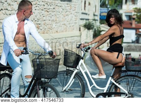 Sexy Girl Rides Bicycle, Urban Background. Attractive Brunette Sit On Bicycle. Couple Of Handsome Ma