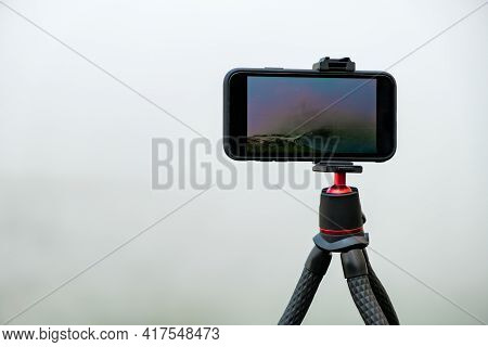Smartphone On The Tripod Taking Photos. Capturing Image Or Time Lapse Of Moving Clouds In The Mounta