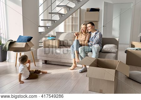 Happy Family Couple New Home Owners With Toddler Kid Child Son Relaxing On Sofa Unpacking Boxes On M