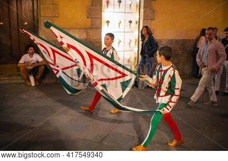 Siena, Italy-october 13, 2018: Locals With Flags Walk Through The Streets In The Center Of Siena