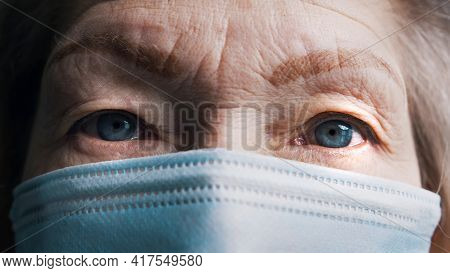 Close Up On The Blue Eyes Of An Old Gray Haired Woman With Face Mask. Vulnerable Aged Person And Cov