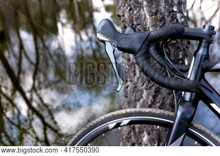 Bicycle. Aluminum Bike. Black Steering Wheel And Black Bike In Nature By The Pond And Tree