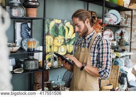 Focused Handsome Bearded Man Using Digital Tablet For Creating Online Catalogue Of Decor Store. Posi