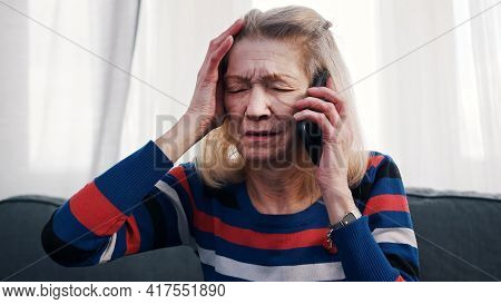 Desperate Old Woman Having Phone Conversation With Tears. High Quality Photo
