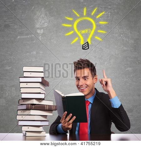 young business man having a great idea while reading an interesting book poster