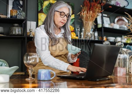 Beautiful Mature Lady Using Modern Laptop While Receiving New Goods For Decor Shop. Grey-haired Sale