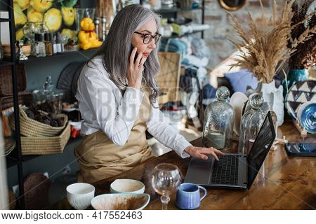 Mature Saleswoman Talking On Mobile And Typing On Laptop While Sitting At Decor Store. Pretty Woman