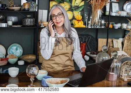Front View Of Mature Confident Saleswoman In Beige Apron Sitting At Decor Shop With Opened Laptop An