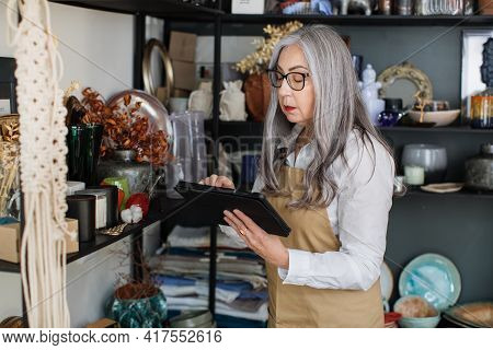 Charming Aged Woman Using Digital Tablet While Doing Inventory At Decor Shop. Competent Saleswoman W