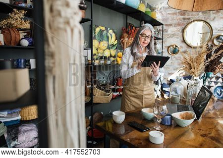 Focused Mature Saleswoman Recounting All Goods At Decor Store. Attractive Woman In Eyeglasses And Ap