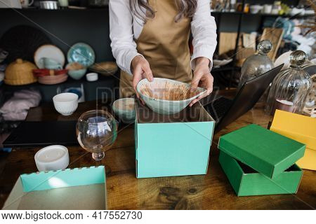 Close Up Of Aged Woman In Apron Packing Goods In Boxes At Decor Store. Competent Saleswoman Preparin