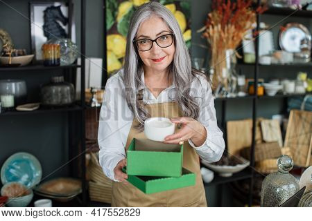 Portrait Of Charming Aged Woman Packing White Candle In Green Box. Professional Saleswoman In Eyegla
