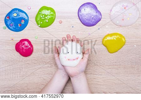 Multi-colored Slimes On The Table. The Child Plays With Mucus. Slime With A Smile. Play Toy - Slime.
