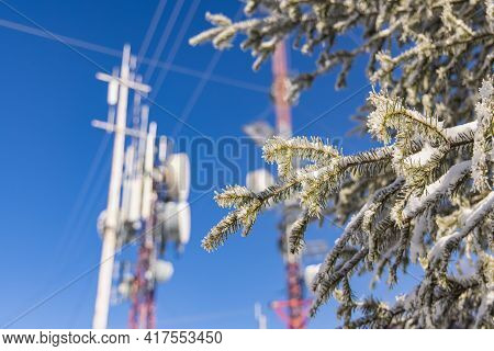 A Side Angle Blurry Shot Of A Cellular Communication Tower, With Antennas And Wires Attached To It,