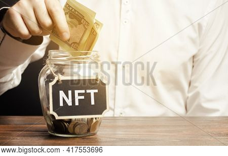Hand Puts Dollar Bills In Glass Jar With The Word Nft. Non-fungible Token. Digitally Represented Pro