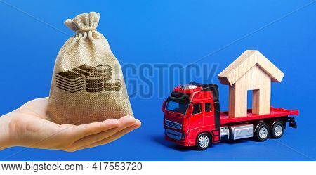 Money Bag, Red Truck Carrier With A House Figure On A Blue Background. Cargo Transportation And Deli