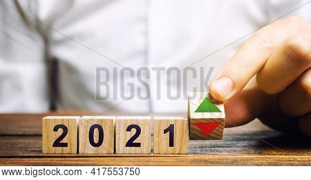 Businessman Puts Wooden Blocks 2021 And Up Or Down Arrow. Summing Up The Year. Financial And Economi